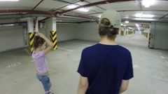 Happy girl and boy roller skate in underground parking, back view Stock Footage