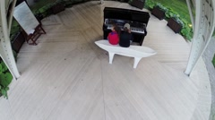 Brother and sister play piano on round stage in green summer park Stock Footage