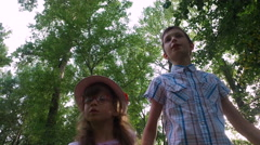 Teen boy and girl child standing in the park. - stock footage