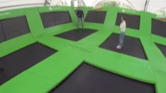 Boy, man, girl, woman jump on trampoline in park Sokolniki. Stock Footage