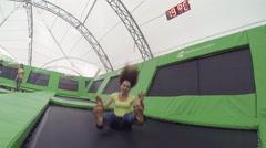 Happy woman jumps on trampoline in park Sokolniki Stock Footage
