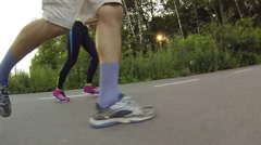 Legs of running man and woman in park, selfie stick Stock Footage