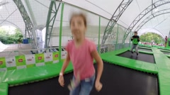 Girl, boy on trampoline in park Sokolniki in Moscow, Russia Stock Footage