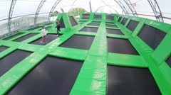 Girl with boy jump together on trampoline in park Sokolniki Stock Footage