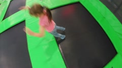 Girl with boy jump around in trampoline center, top view Stock Footage