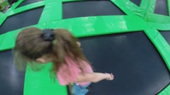 Girl in pink jumps around camera on trampoline, top view Stock Footage