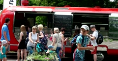 People buy food from the red food truck Stock Footage