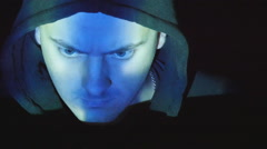 Hooded hacker working on a computer, binary code projecting on his face - stock footage