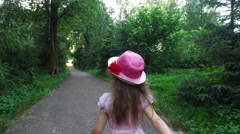Teen boy and girl child running toward each other along the path in the park. - stock footage