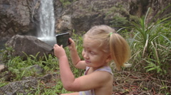 Closeup Little Girl Plays with Phone on Stone against Waterfall - stock footage