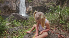 Closeup Little Girl Plays on Stone against Waterfall Cascade - stock footage