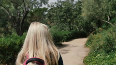 Young woman in sunglasses with backpack walking in park Stock Footage