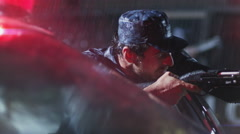4K Policeman with gun on the rain. Police surrounding. Slow Motion. Stock Footage