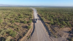 Aerial view of an approaching tractor trailer on a dirt road Stock Footage