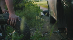 A strong man takes the wheel of a car in the woods, close up Stock Footage