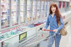 Smiling woman pushing trolley in aisle - stock photo
