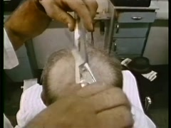 Balding man getting a hair cut at barber shop, 1970s Stock Footage