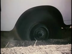Closeup of  car stuck on dirt road with back wheel spinning, 1970s Stock Footage