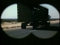 Zoom in shot of border sign by country road seen through binoculars, 1970s Stock Footage