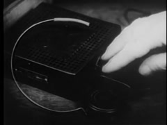 Close-up of person picking up hearing aid, 1930s - stock footage