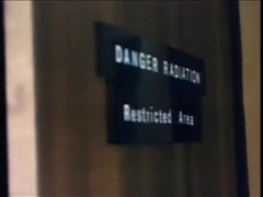 Close-up of Danger Radiation Restricted Area sign on closing door, 1970s Stock Footage