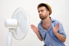 Flushed man feeling hot in front of a fan - stock photo