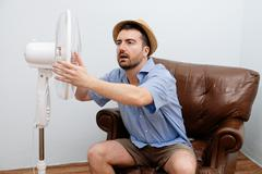 Flushed man feeling hot in front of a fan Stock Photos