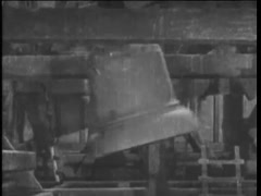 Close-up of  large bells swinging in church rafters, 1920s Stock Footage