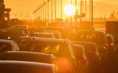 Cars are in traffic jam during a beautiful golden sunset. - stock photo