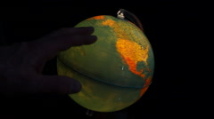 Political world globe rotating by hand on black background Stock Footage