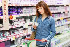 Customer looking at a product in the dairy section - stock photo