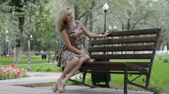 Young blond girl in dress posing in summer Park, sitting on the bench - stock footage