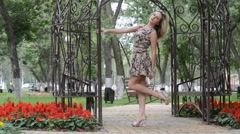Young blonde girl in a summer dress posing in the Park near the gazebo - stock footage