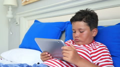 Child lying on a bed and using digital tablet computer 6 Stock Footage