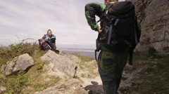 4K Active couple on a hike sit down to rest on cliff top Stock Footage