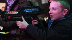 young  boy playing video games at indoor amusement park. - stock footage