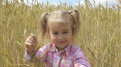 Cute little girl walking through wheat field  stalks and smiling. Slow motion Stock Footage