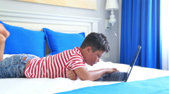 Child lying on a bed and using laptop computer 5 Stock Footage