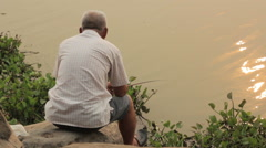 Unrecognized old man sitting by the lake Stock Footage