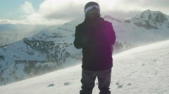 Person skis down a mountain with beautiful sky in background Stock Footage