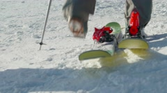 Person puts on skis in the snow Stock Footage