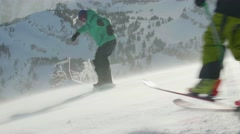 Skiing and snowboarding at top of mountain Stock Footage