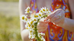 Woman in red dress collects a wreath of wildflowers in meadow of flowers Stock Footage