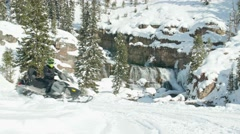 Close up of snowmobiles driving past a waterfall 2 Stock Footage