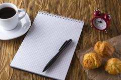 Blank notebook, alarm clock,eclairs and coffee cup. Stock Photos