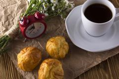 Eclair, coffee cup, alarm clock and charmomile. - stock photo