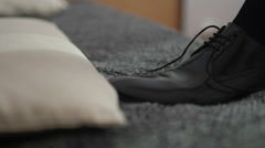 Man tying patent leather shoes Stock Footage