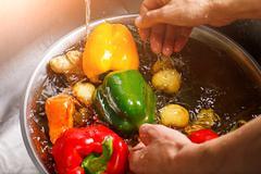 Hands washing paprika and potatoes. - stock photo