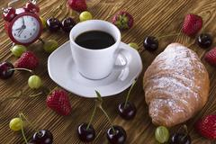 Alarm clock and breakfast with berries, coffee , croissant. - stock photo
