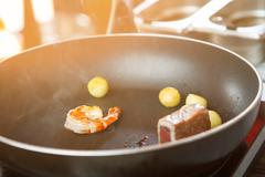 Shrimp on black frying pan. Stock Photos